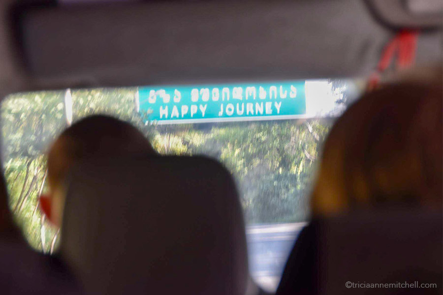 "A street sign reading ""Happy Journey"" in English and in Georgian, is visible through the windshield of a minivan."