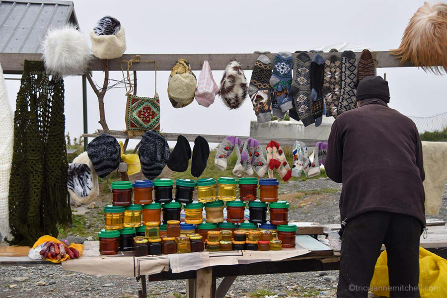 A man sells souvenir items at the Russia–Georgia Friendship Monument. On the table there are 3 rows of jarred honey stacked on one another, along with wool socks, fuzzy hats, and a cross-stitched purse.
