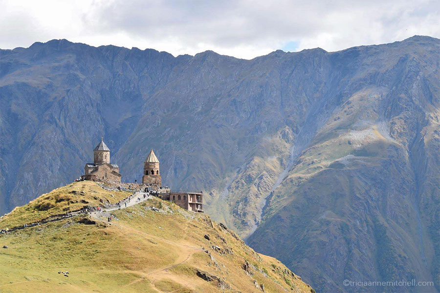 The two rounded towers of the Gergeti Trinity Church rise from a grassy and rocky hilltop. In the background are the steep slopes of the Caucasus Mountains.