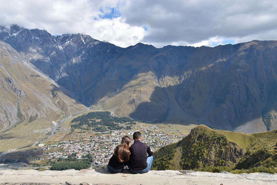 Two people (whose backs are facing the camera) look at the view from the Gergeti Trinity Church. Large mountains are visible off in the distance, and you an see the tiny town of Kazbegi below.