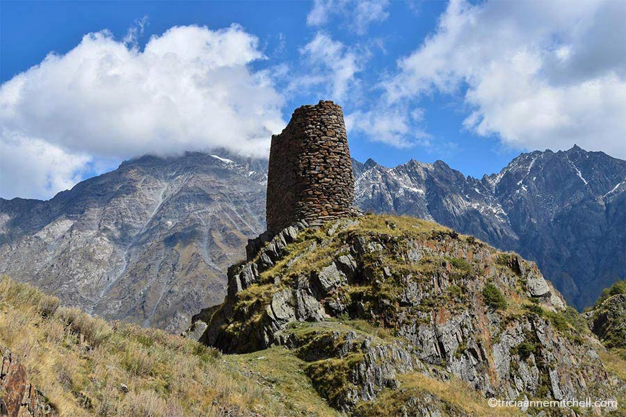 The crumbling remains of a stone watchtower rise from a rocky outcrop in the Caucasus Mountains near the Gergeti Trinity Church. There is a blue sky overhead, with some clouds.