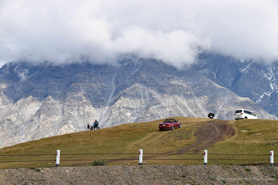 A car and a van drive up the grassy slopes near the Gergeti Trinity Church, marring the landscape. In the background are steep mountain slopes — some covered with a bit of snow.