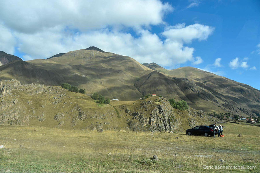 A car parked on a grassy lawn near the Georgian Military Highway. There are greenish-brown mountain slopes in the background. A tiny house sits on one hilltop.