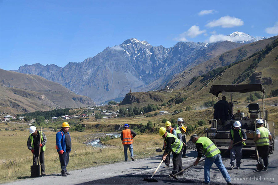 Construction men repair a stretch of road along the Georgian Military Highway. There are snow-capped mountain peaks and a stone watchtower off in the distance.
