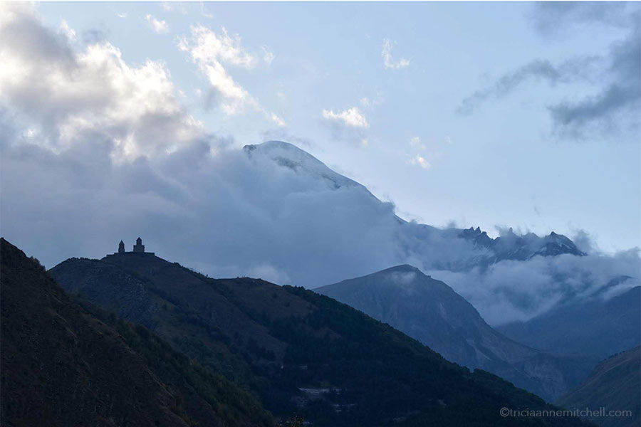 The Gergeti Trinity Church is seen in silhouette form against a cloudy backdrop. Snowy Mount Kazbek is only partially visible.