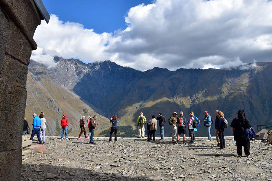 About 15 visitors stand on a rocky platform overlooking a mountainous backdrop near the Gergeti Trinity Church in Georgia. The sky is mostly cloudy.