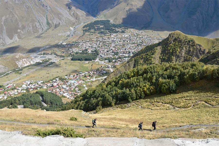 Three hikers walk on a dirt path as they make their way up to the Gergeti Trinity Church. You can see the rooftops of Gergeti and Kazbegi below, and there is a green hilltop.