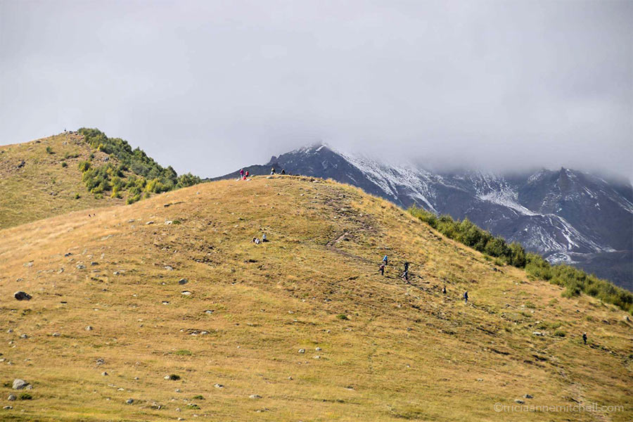 About 10 hikers make their way down a trail. Georgia's Mount Kazbek is concealed by clouds.