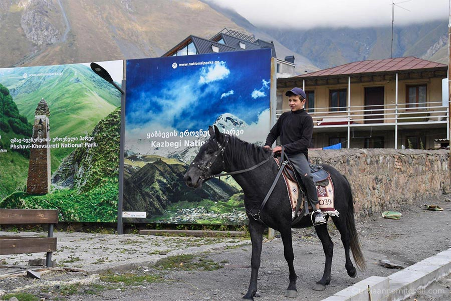 A young boy rides a black horse on a sidewalk in the town of Kazbegi (Stepantsminda), Georgia. There are 2 tourism billboards on his right, and a house in the background.