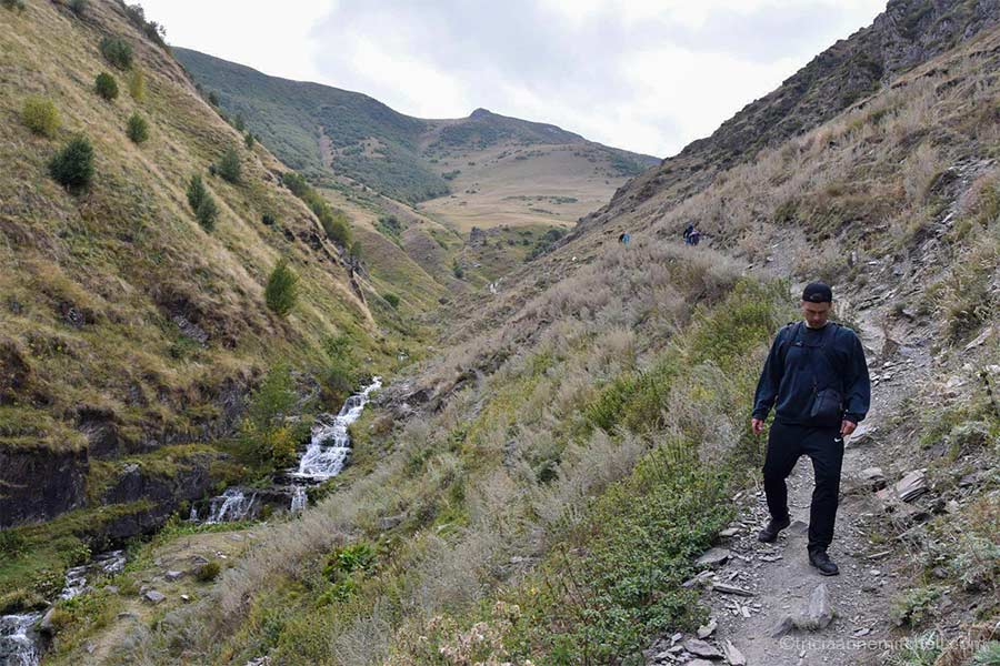 A man hikes down a rocky/dirt path alongside a stream in the Caucasus Mountains.
