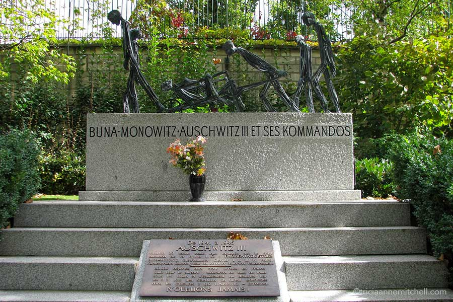 """A rectangular headstone features abstract concentration camp figures. Inscribed on it are the words """"Buna Monowitz Auschwitz III et ses kommandos."""" Below another plaque reads, """"Auschwitz, n'oublions jamais."""""""