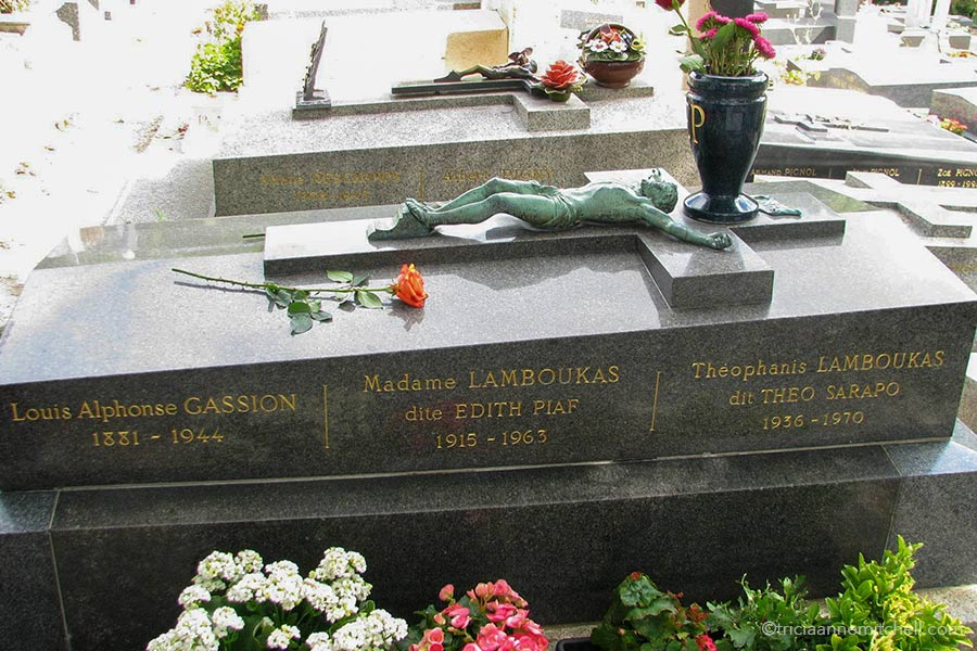 """Edith Piaf's grave in Paris' Pere Lachaise Cemetery. There is a copper crucifix laying on top of the gray memorial and an urn filled with flowers is set on top of the memorial. The grave reads: """"Louis Alphonse Gassion 1881-1944, Madame Lamboukas dite Edith Piaf 1915-1963, Theophanis Lamboukas dit Theo Sarapo 1936-1963"""""""