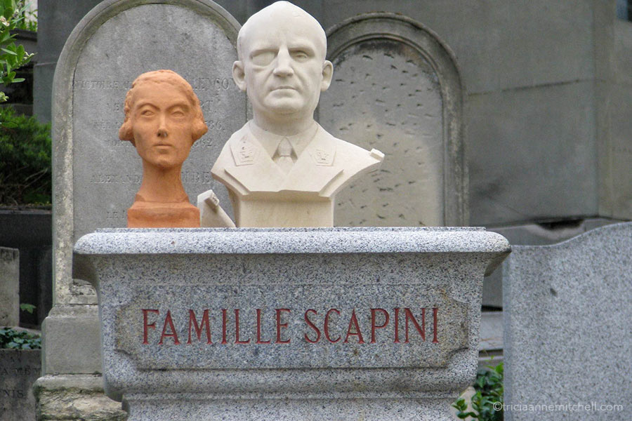 """Two busts - one female and orangish, and another male and white - stand atop a headstone. The words """"Famille Scapini"""" are written on it."""