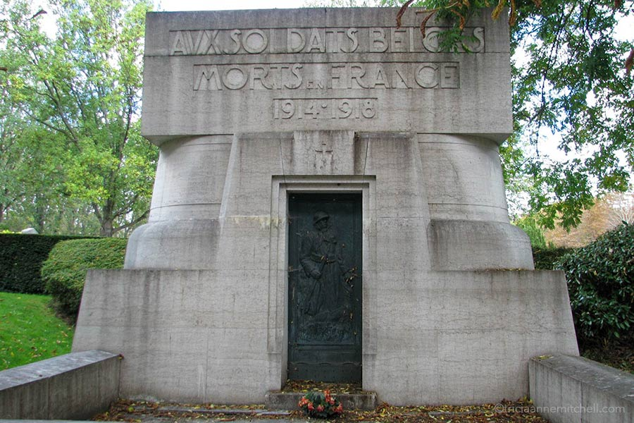 "A grey stone monument with a dark green metal door in the Pere Lachaise Cemetery in France. The carved words on the top of it read: ""Monument aux soldats belges morts en France."""
