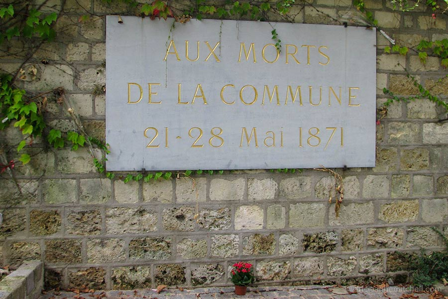 "A sign on a stone wall in Père Lachaise Cemetery reads: ""Aux morts de la Commune 21-28 Mai 1871"""