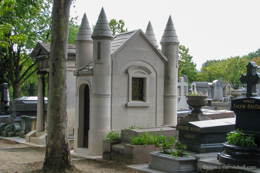 A stone mausoleum resembling a small castle with four towers sits beside other headstones in the Pere Lachaise Cemetery.