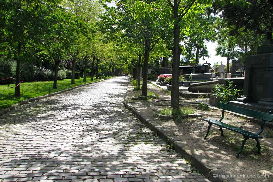 A brick street in Pere Lachaise Cemetery is partially cast with shadows from green trees overhead. To the right there is a green bench. Headstones are visible in the background.
