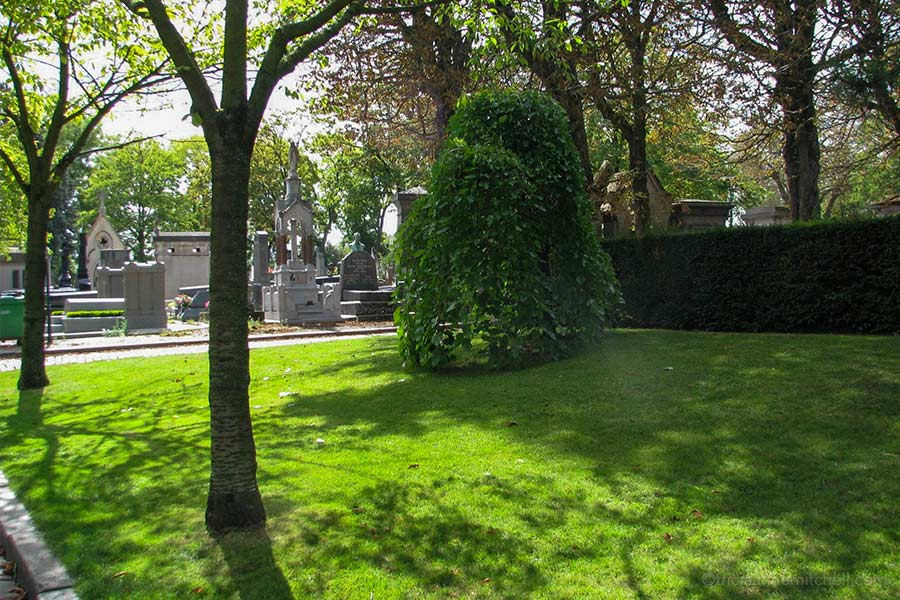 Trees cast shadows on the green lawn of Paris' Pere Lachaise Cemetery. There are a few headstones and mausoleums in the background.