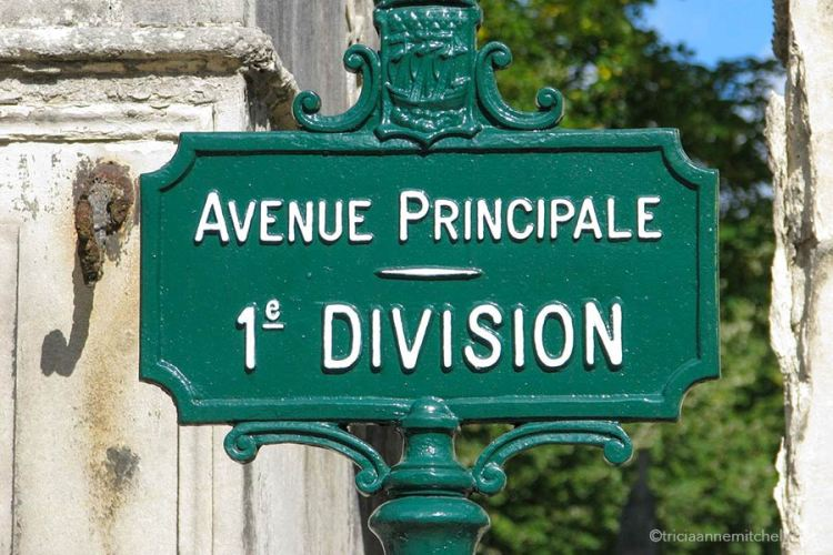 A decorative green iron sign in Pere Lachaise Cemetery reads: Avenue Principale 1e Division.